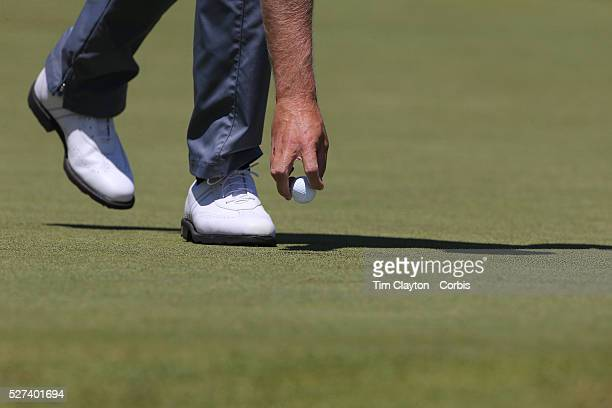 A golfer removes the golf ball from the hole after putting Photo Tim Clayton