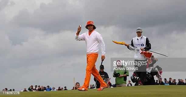 US golfer Rickie Fowler acknowledges the crowd as he walks across a green on the final day of the 140th British Open Golf championship at Royal St...