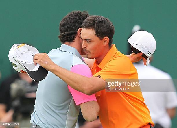 US golfer Rickie Fowler embraces Northern Ireland's Rory McIlroy on the 18th green after McIlroy wins the 2014 British Open Golf Championship at...