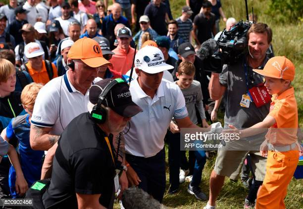US golfer Rickie Fowler gets encouragement from a fan as he walks out from the rough on the 8th hole during his third round on day three of the Open...
