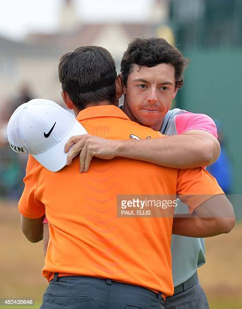US golfer Rickie Fowler hugs Northern Ireland's Rory McIlroy on the 18th green after McIlroy wins the 2014 British Open Golf Championship at Royal...