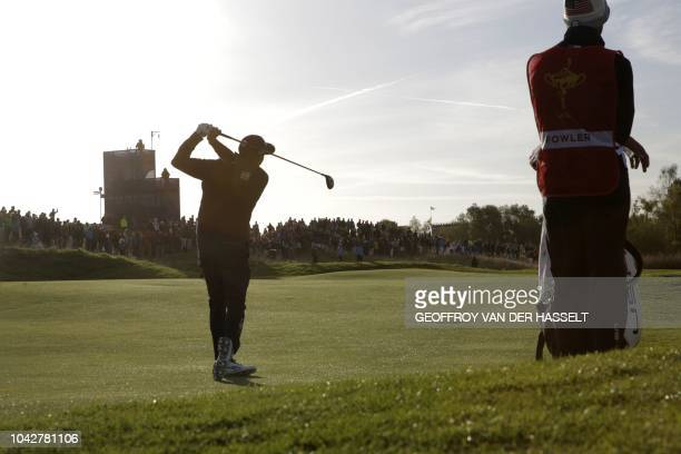US golfer Rickie Fowler plays a fairway shot during his fourball match on the second day of the 42nd Ryder Cup at Le Golf National Course at...