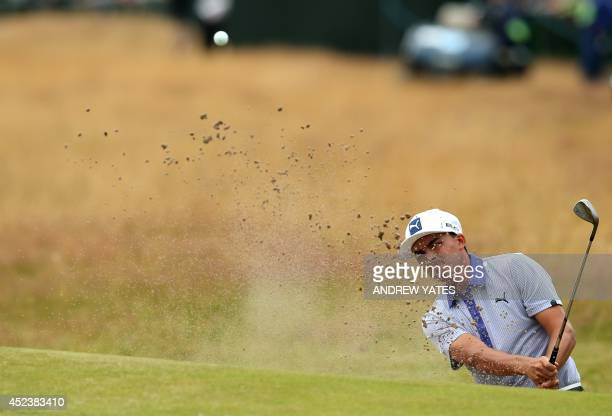 US golfer Rickie Fowler plays from a bunker on the 18th hole during his third round 68 on day three of the 2014 British Open Golf Championship at...