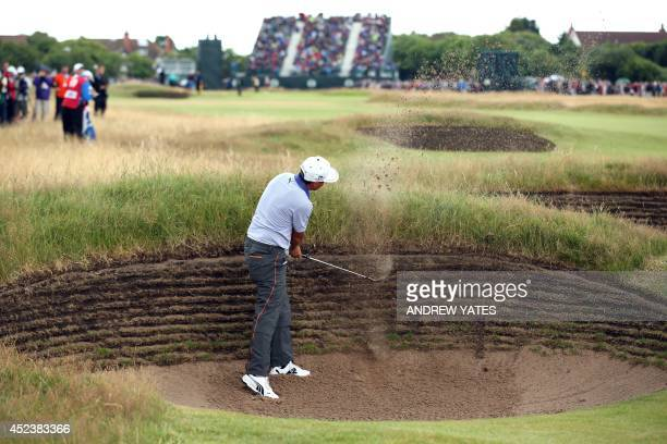 US golfer Rickie Fowler plays out of a bunker on the 17th hole during his third round 68 on day three of the 2014 British Open Golf Championship at...
