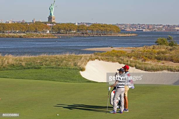 USA golfer Rickie Fowler plays the 14th hole with the Statue of Liberty in the background during the first round of the Presidents Cup on September...