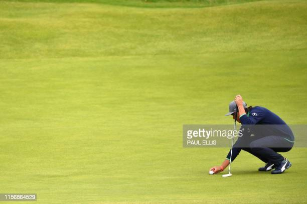 US golfer Rickie Fowler prepares to putt on the 17th green during the third round of the British Open golf Championships at Royal Portrush golf club...