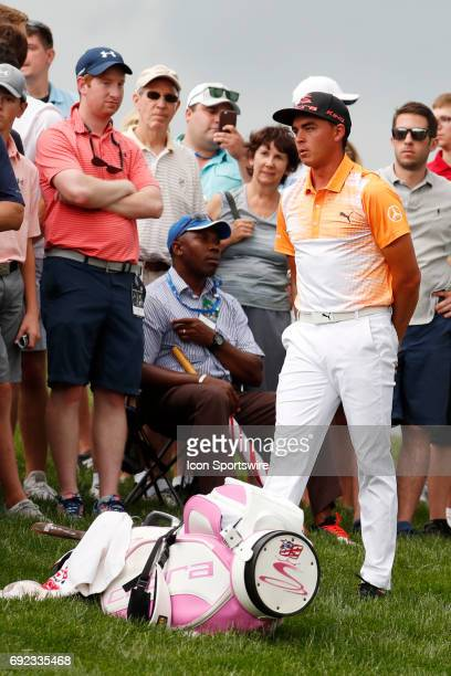PGA golfer Rickie Fowler waits in the rough on the 13th hole for a ruling by an official as play is stopped for a weather delay during the Memorial...