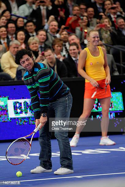 Golfer Rory McIlroy of Northern Ireland joins his girlfriend Caroline Wozniacki of Denmark on the court and plays a shot against Maria Sharapova of...