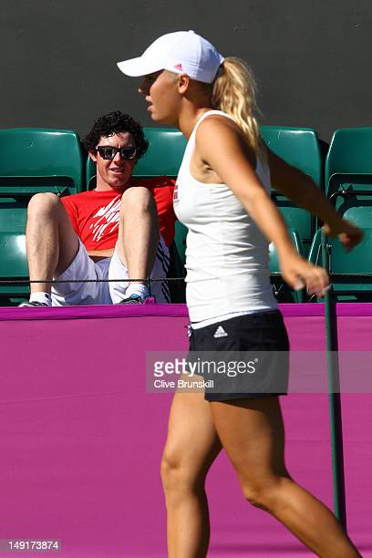 Golfer Rory McIlroy watches girlfriend Caroline Wozniacki of Denmark during a practice session ahead of the 2012 London Olympic Games at the All...