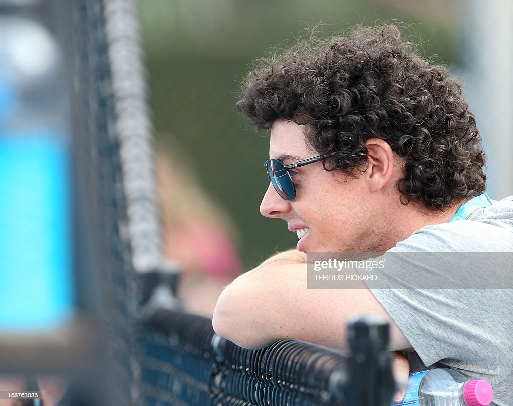 Golfer Rory Mcllroy of Northern Ireland watches his girlfriend Caroline Wozniacki of Denmark during a training session in Brisbane on December 28, 2012, for the upcoming Brisbane International tennis tournament. The top international men's and women's players are using the Brisbane International as a build-up to the Australian Open, which runs from January 14 to 27. AFP PHOTO / Tertius PICKARD USE