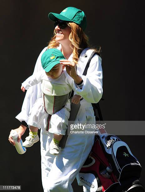 Golfer Rory Sabbatini's wife Amy carries their son Bodhi while also serving as his caddie during the Par 3 Contest prior to The Masters at Augusta...