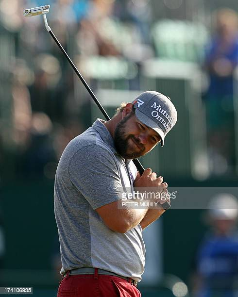 Golfer Ryan Moore reacts to missing a putt on the 18th green during the third round of the 2013 British Open Golf Championship at Muirfield golf...