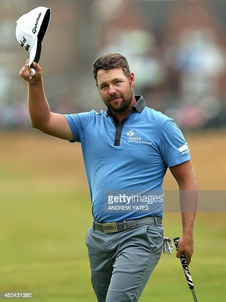 Golfer Ryan Moore waves to the crowd on the 18th green after his fourth round 68, on the final day of the 2014 British Open Golf Championship at...