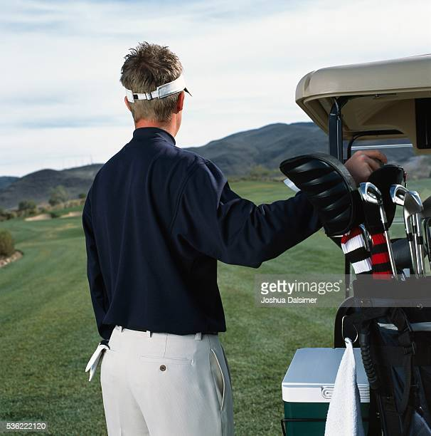 Golfer selecting golf club