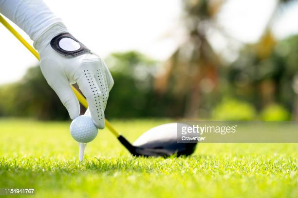 golfer set the golf ball on the tee pin with club on course while on summer vacation. hand holding golf ball with tee on course, tee off, copy space on right side - カントリークラブ ストックフォトと画像