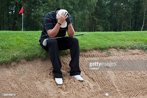a golfer sitting at the edge of sand trap, head in hands - bunker stock pictures, royalty-free photos & images