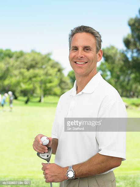 golfer standing on golf course, portrait - polo shirt stock pictures, royalty-free photos & images