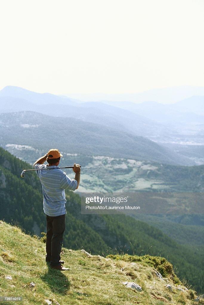 Golfer standing, overlooking mountainous landscape : Stock Photo