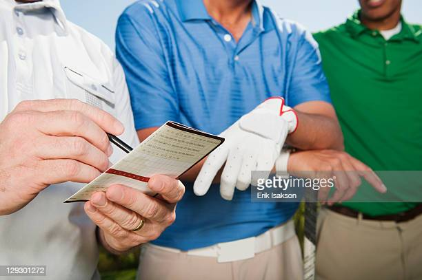 Golfer standing with friends writing in golf score card