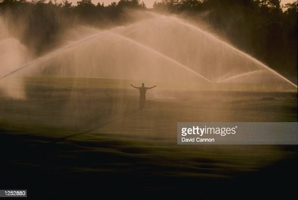 A golfer stands on the golf course as the sprinklers run prior to a round of the 1993 Volvo PGA Championships at the Wentworth Golf Club in England...