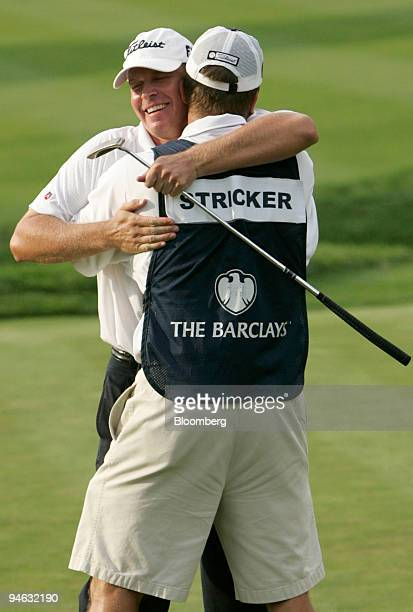 Golfer Steve Stricker hugs his caddie after sinking a birdie putt on the 18th hole of Barclays Classic golf tournament to win the championship at...