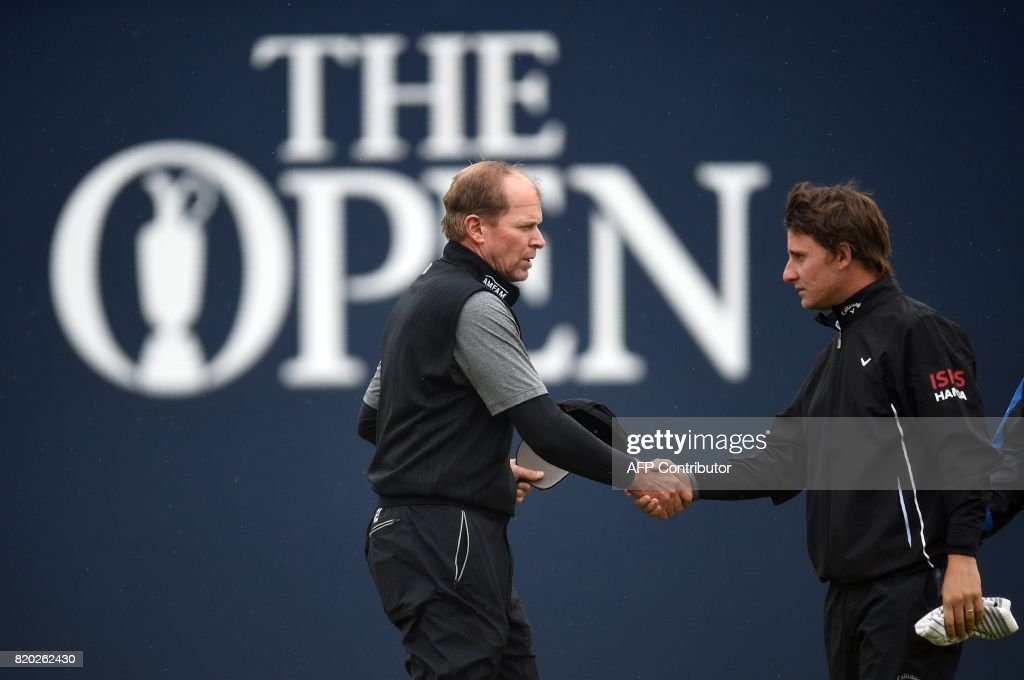 US golfer Steve Stricker (L) shakes hands with Argentina's Emiliano Grillo on the 18th green after their second rounds on day two of the Open Golf Championship at Royal Birkdale golf course near Southport in north west England on July 21, 2017. / AFP PHOTO / Oli SCARFF / RESTRICTED