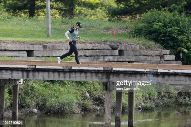 LPGA golfer Sung Hyun Park runs across a bridge to the 9th tee during the final round of the Indy Women In Tech on August 19 2018 at the Brickyard...