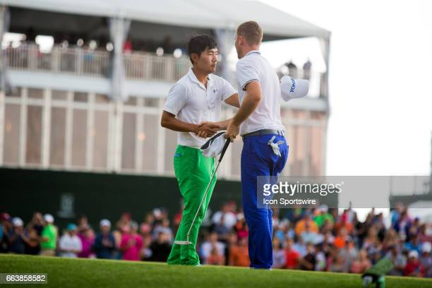 PGA golfer Sung Kang shakes hands with Russell Henley on the 18th green after Henley won the Shell Houston Open on April 02 2017 at Golf Club of...