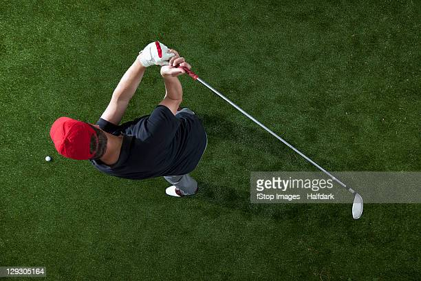 A golfer swinging a golf club, overhead view