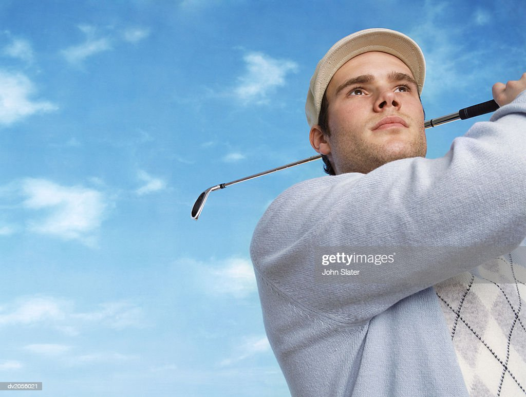 Golfer Swinging a Golf Club : Stock Photo