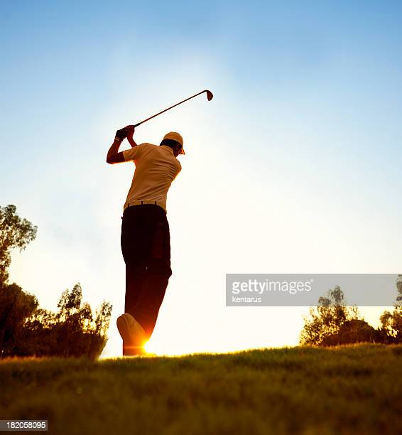 Golfer swinging at beautiful sunset