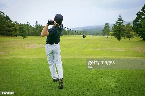 Golfer swinging club, rear view,