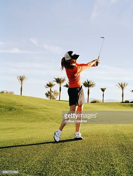 Golfer swinging golf club