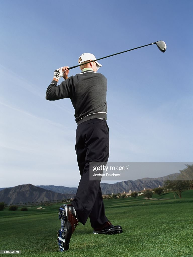 Golfer swinging golf club : Stock Photo