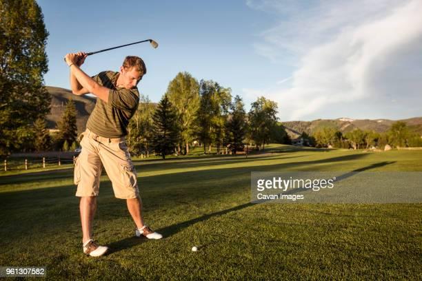 golfer swinging golf club while standing on grassy field - golfschläger stock-fotos und bilder