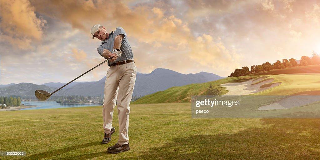 Golfer Swings at Sunset : Stock Photo