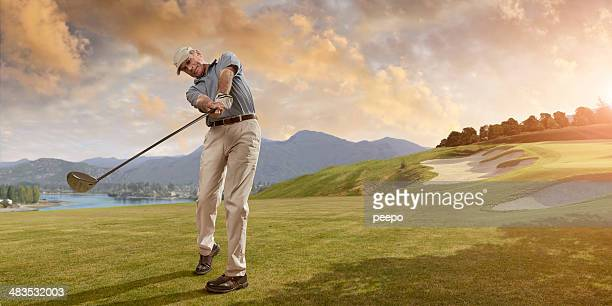 golfer swings at sunset - golf swing stock pictures, royalty-free photos & images