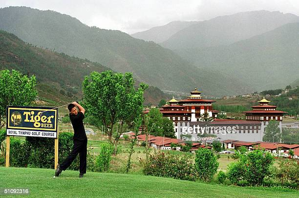 Golfer Takes A Swing At The Royal Thimpu Golf Course May 20, 2000 In Thimpu, Bhutan. The Trashichhoe Dzong In The Back Ground Is A Backdrop For...