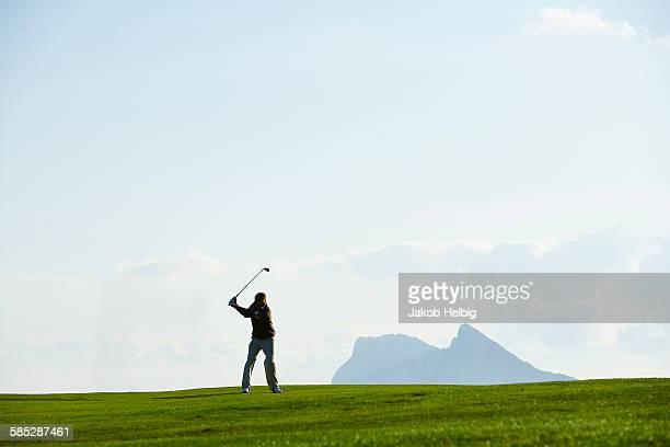 Golfer taking golf swing in front of mountain range
