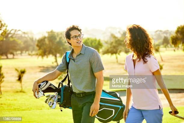 golfer talking to friend at golf course - パッティンググリーン ストックフォトと画像