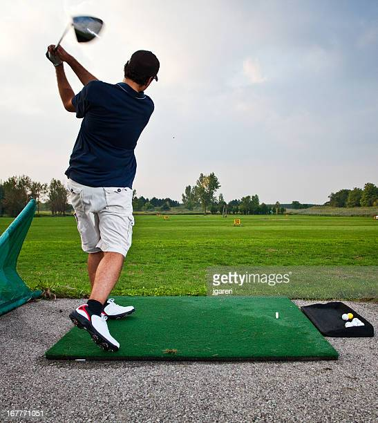 golfer teeing off at a driving range - driving range stock pictures, royalty-free photos & images