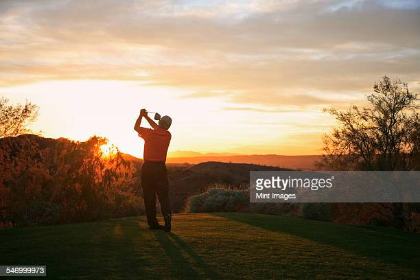 golfer teeing off into the sunset on the golf course. - golpear desde el tee fotografías e imágenes de stock