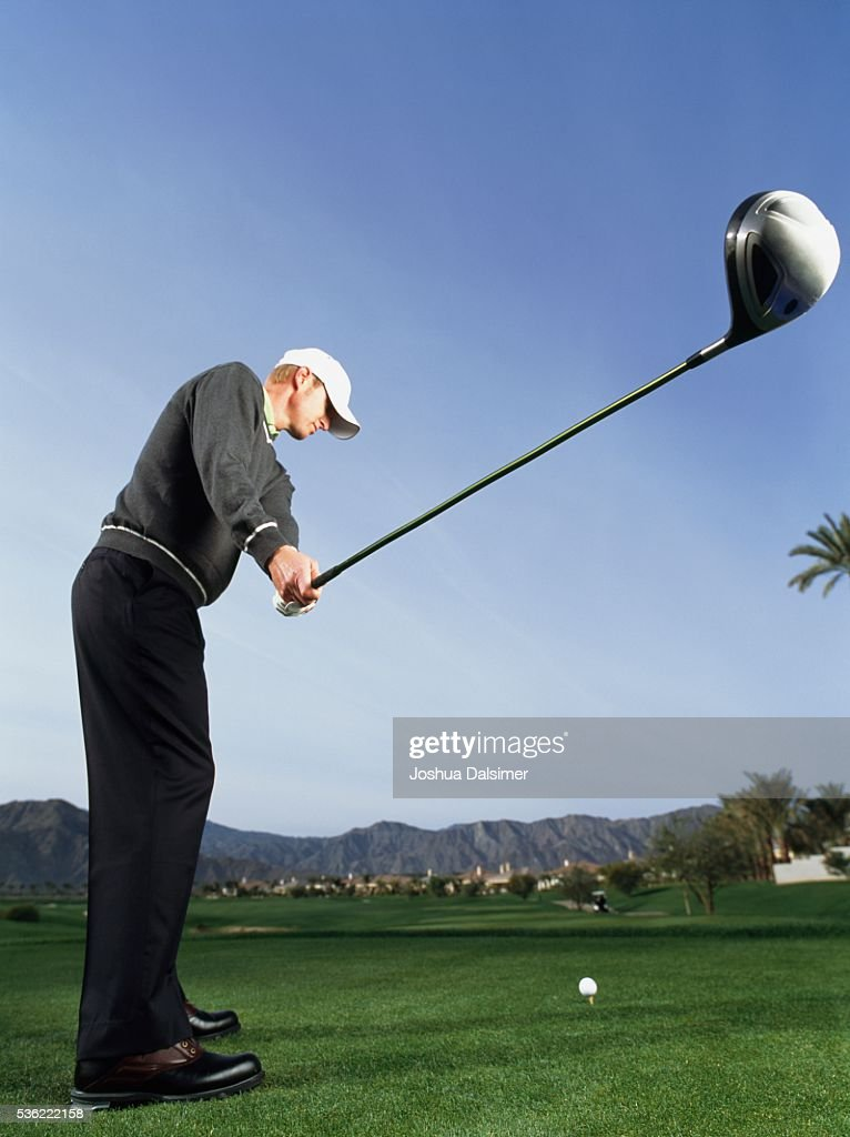 Golfer teeing off : Stock Photo