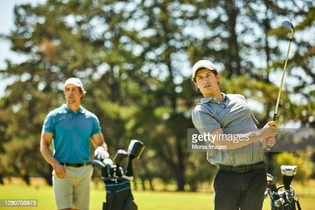 golfer teeing off while friend standing in golf course - play off stock pictures, royalty-free photos & images