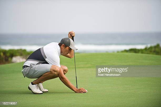 a golfer tees up his ball - green shorts stock photos and pictures