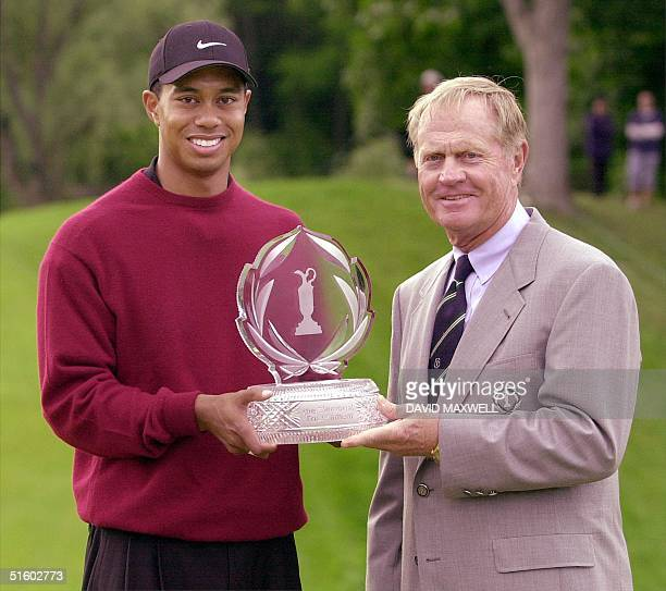 US golfer Tiger Woods accepts the winner's trophy from Jack Nicklaus 03 June at the Memorial golf tournament at Muirfield Village Golf Club in Dublin...