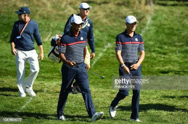 Golfer Tiger Woods and US golfer Justin Thomas walk during a practice session ahead of the 42nd Ryder Cup at Le Golf National Course at...