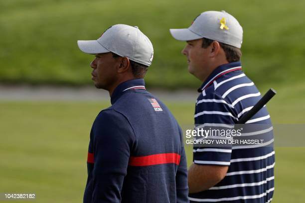 US golfer Tiger Woods and US golfer Patrick Reed look on during their fourball match on the first day of the 42nd Ryder Cup at Le Golf National...