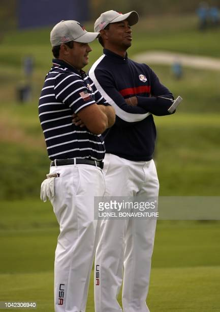 US golfer Tiger Woods and US golfer Patrick Reed react during their fourball match on the first day of the 42nd Ryder Cup at Le Golf National Course...
