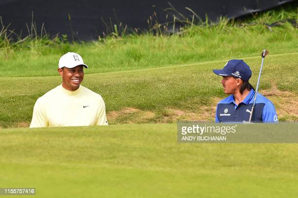 US golfer Tiger Woods and US golfer Rickie Fowler chat in a greenside bunker on the 13th hole during a practice session at The 148th Open golf...